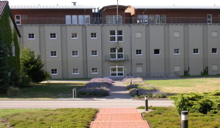 SDEI Institutsgebäude. Blick auf den Haupteingang mit Heuschreckenlogo.